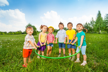 Six funny children holding one hoop together
