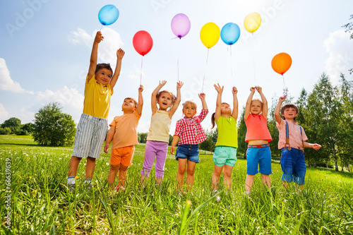 Happy kids with balloons and arms up in the sky - 66639639