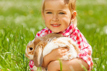 Cute girl cuddling rabbit in green field