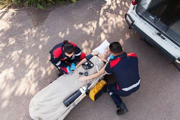 paramedic team providing first aid to unconscious woman