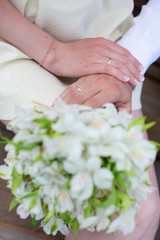 Hands of bride and groom holding wedding bouquet