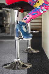 Woman sitting on bar stool in high heel ankle boots