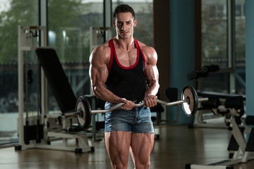 Bodybuilder Performing Biceps Curls With A Barbell