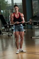 Muscular Men Doing Heavy Weight Exercise For Biceps
