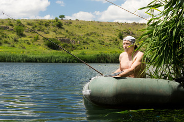 Elderly man fishing shirtless on a tranquil lake