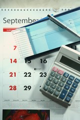 Calendar, checkbook, calculator, money and a ballpen