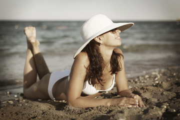 Young woman sunbathes laying on sand.