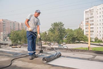 Worker make waterproofing of seams on bridge