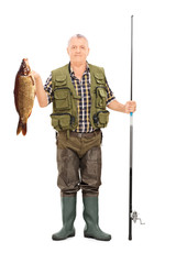 Fisherman holding a fish and a fishing rod