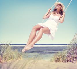 Beautiful Cheerful Woman Swinging by the Beach