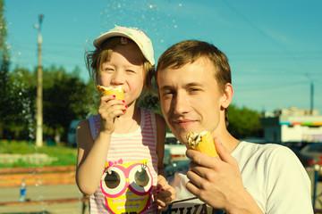Папа с дочкой кушают мороженое летом на улице