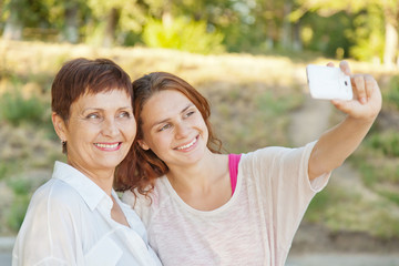 mother and adult daughter are doing selfie on phone
