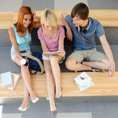Three college students looking tablet top view