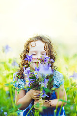 Happy child in a field with a bouquet of wildflowers.