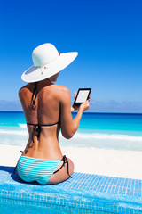 Beautiful woman from back reads kindle with hat