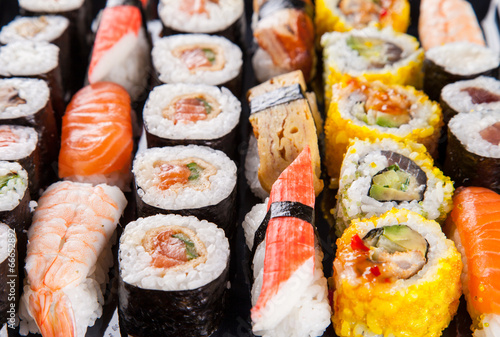 canvas print picture Delicious sushi pieces served on black stone