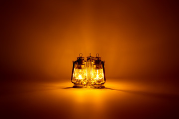 Burning three kerosene lamps background, concept gold light