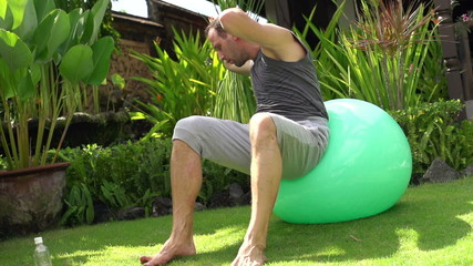 Man doing sit-ups on fitness ball in garden, super slow motion