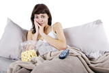 young teenager watching movies in bed with popcorn