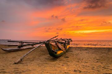 Traditionelles Auslegerboot bei Sonnenuntergang am Strand