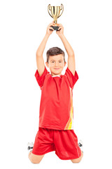Joyful little boy holding a trophy above his head