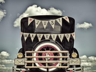 Retro styled image of an old car with just married decoration