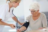 Doctor checking elderly woman's blood pressure