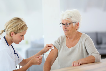 Nurse making vaccine injection to elderly patient
