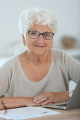 Elderly woman using laptop computer at home