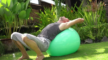 Man stretching, relaxing on fitness ball