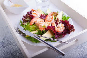 Avocado shrimp salad with mustard sauce on a tray