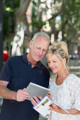aktives paar mit tablet-pc und reiseführer