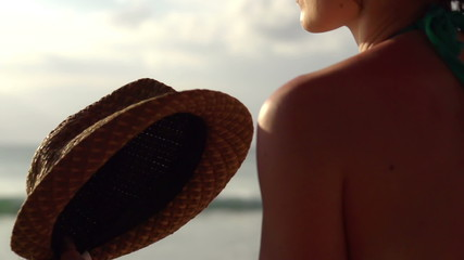 Woman cooling herself with hat by the sea, super slow motion