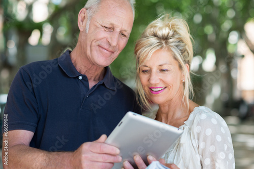 Leinwanddruck Bild aktives seniorenpaar schaut auf tablet-pc