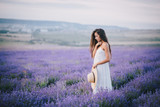 Fototapety Beautiful young woman posing in a lavender field