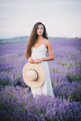 Beautiful young woman posing in a lavender field