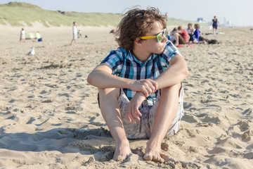 Portrait of  teenage guy siting on sand