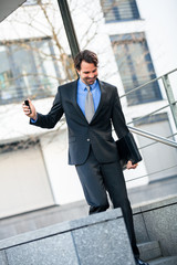 Smiling businessman walking down stairs