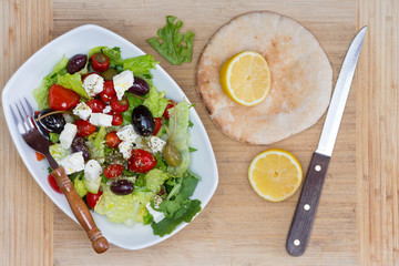 Fresh Mediterranean salad, lemon and pita bread