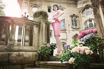 Beautiful lady in pink dress, in front of an old mansion