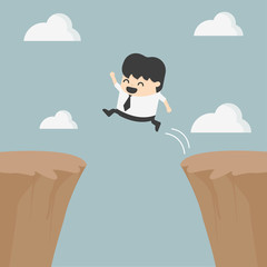 Businessman jumping over the cliff