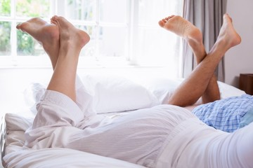 Couples legs lying on bed