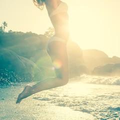 Beautiful jumping blonde in white bikini at the beach