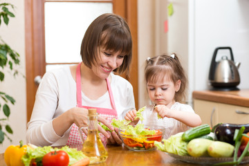Young mother and her kid making vegetable salad