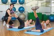 Fit women working out together in studio with trainer