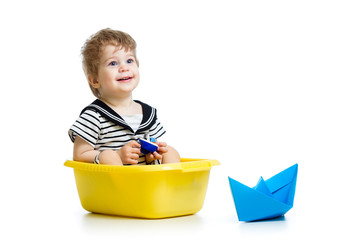 sailor kid sitting inside washbowl