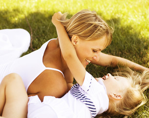 mother with daughter having fun on grass