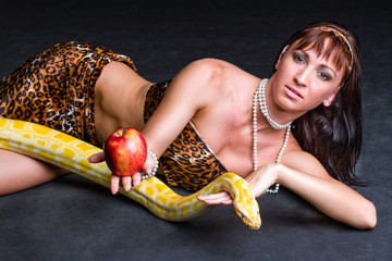 Woman with a snake eating red apple