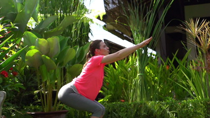 Woman doing squats, exercising in garden, super slow motion