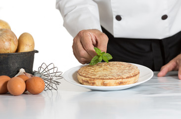 Chef decorating a potato omelette